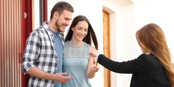 Happy couple of renters receiving house keys from successful landlord.